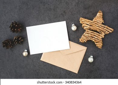 Card and envelope with Christmas decorations, top view. Holiday mock up with postcard.