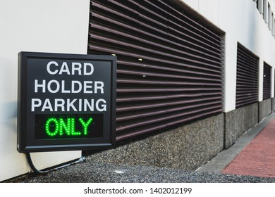 Card holder parking only sign in front of a garage door