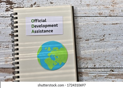 """A card with an illustration of the Earth and the words """"ODA (Official Development Assistance)"""" is placed on the table."""