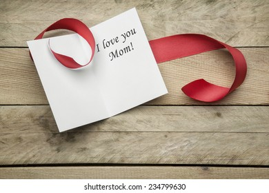 Card I love you Mom and ribbon on wooden background