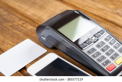 Card machine, white smartphone, blank white credit card on wooden surface