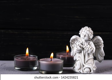 Card for mourning, death, sorrow. Little angel and burning candles on  dark background. Selective focus. Place for text.