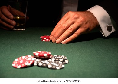 Card player in casino with chips and drink