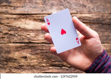 card player holds aces on a wooden background with space for text