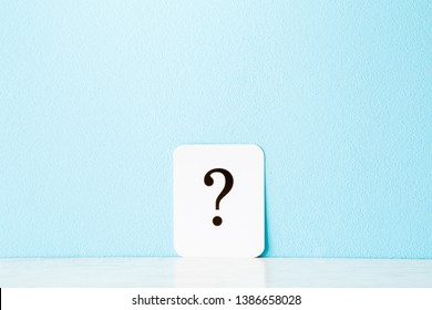 Card of question mark on pastel blue background. Empty place for  text, plans, thoughts or other good ideas for making decision. Front view.