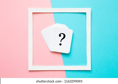 Card of question mark in white frame on pastel pink and turquoise blue background. Soft light color. Teenagers issues. Boys and girls problems and solutions concept.