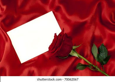 card with a red rose on red silk background