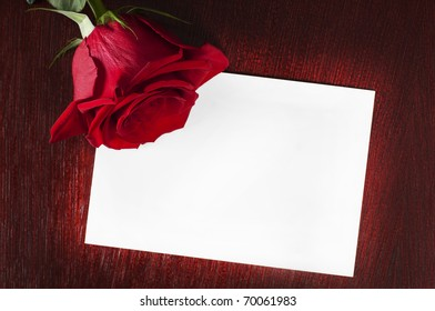 card with a red rose on the wooden table