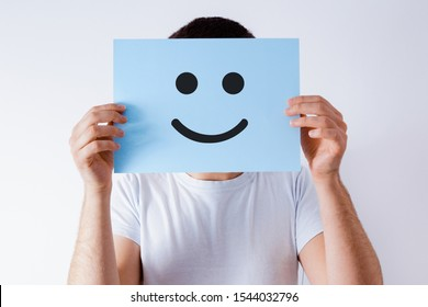Card with a smiley face on the background of a man. The concept of satisfaction, covering real emotions with artificial ones. Blue card with a smiley face.