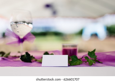 Card with space for text placed on decorated table for celebration,very shallow depth of field - Focus on the card. In background blurred glass of water, ribbon, flower, tablecloth and green garden.