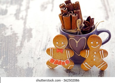 card for St. Valentine's Day, ginger gingerbreads near a mug with the image of heart,in it a linking of cinnamon,an anisetree asterisk, on a light wooden background, close up with a place for the text
