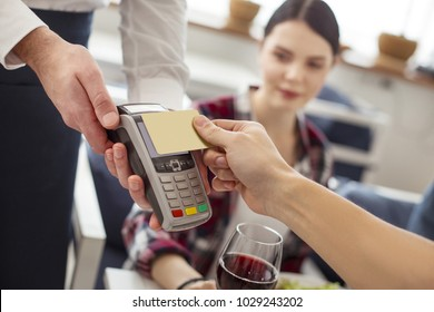 Card terminal. Attractive alert smiling young woman wearing casual clothes and having dinner with her friends and one of them paying by card