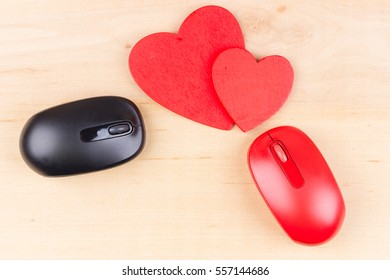 Card for Valentine's Day with two red hearts and two computer mice on wooden background