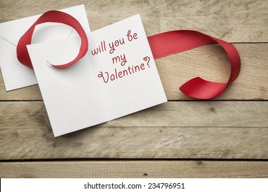 Card Will you be my valentine on wooden background