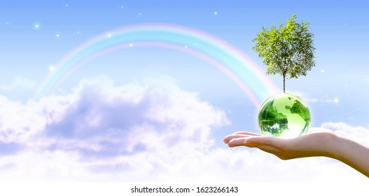 Card for World Earth Day. Planting trees, Ozone Day concept. Saving environment, save and protect green planet and ecology. Earth globe and growing tree in hand on stars sky and rainbow background. - Shutterstock ID 1623266143