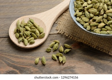 Cardamom in a ceramic bowl on the table and a wooden spoon
