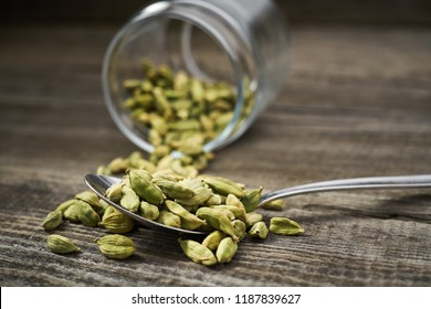 Cardamom in a metal spoon on a gray wooden background.