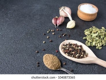 Cardamom, saffron, coriander, pepper, garlic, salt on black stone background. Classic mixed spices for cooking. Top view with copy space.