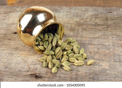 Cardamom spice in golden metal pot on rustic wood background