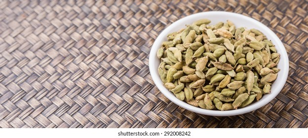 Cardamom spices in white bowl over wicker background