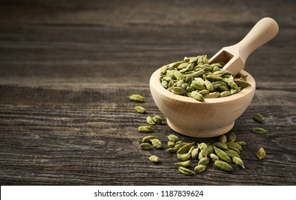 Cardamom  in a wooden scoop . Cardamom  in a wooden shovel  on a gray wooden background.