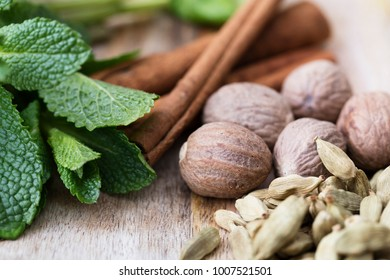 Cardamon, nutmeg, mint leaves and cinnamon sticks close-up on rustic wooden surface