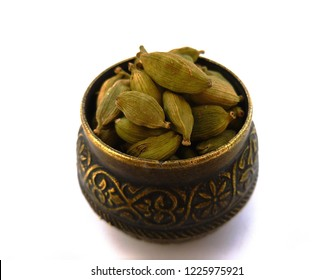 Cardamon pods. Fresh dried green cardamon seeds spice in an old copper bowl isolated on white background.