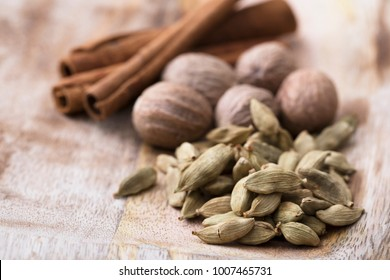 Cardamon seeds with nutmeg and cinnamon sticks on rustic wooden surface.