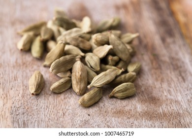 Cardamon seeds on rustic wooden surface.