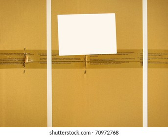 Cardboard background of a closed package box with tapes and straps