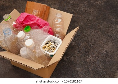 Cardboard Box or carton filled with plastic bottle , plastic bag ,waste paper ,ring pull or pull tab , on dark concrete background  wait for reuse or recycle , save environment and green concept