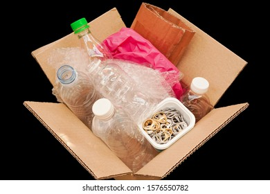 Cardboard Box or carton filled with plastic bottle , plastic bag ,waste paper ,ring pull or pull tab , on black background  wait for reuse or recycle , save environment and green concept