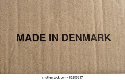 Cardboard box close up with black text, Made in Denmark.