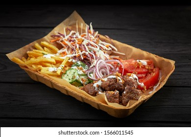 Cardboard box filled with barbecue food: kebab, vegetables, french fries, tomato and mayonnaise sauce