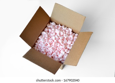 Cardboard box full of pink styrofoam packing peanuts