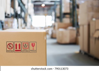 Cardboard box with goods on the background of a blurry modern warehouse