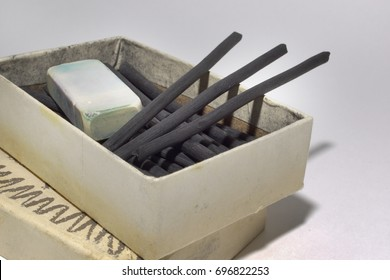 cardboard box with natural charcoal sticks and dirty eraser. vintage art materials for draw. Closeup