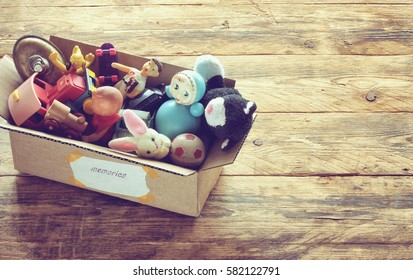 "cardboard box with old dusty toys, glued note with the word ""memories"" on the wooden table."