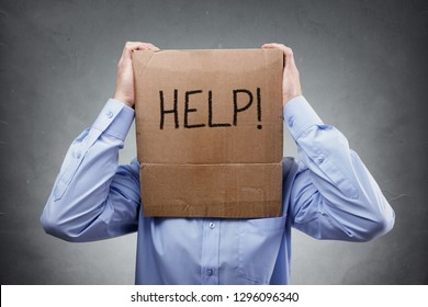 Cardboard box on businessman head asks for help concept for problems, support, overworked or stress