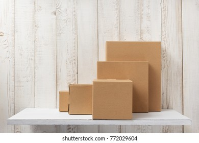 cardboard box on white wooden shelf