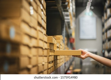 Cardboard box package with blur hand of Asian shopper woman picking product from shelf in warehouse. customer shopping lifestyle in department store or purchasing factory good concepts.