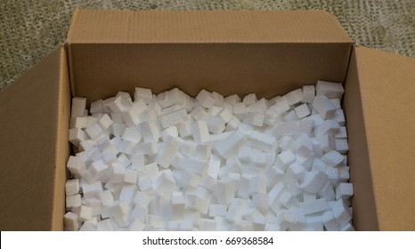 cardboard box with packing foam pellets white polystyrene foam, styrofoam popcorn or packing noodles used to cushion the contents of packages while shipping commonly made of expanded polystyrene foam