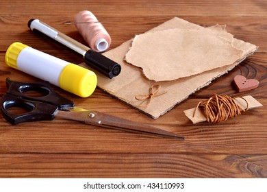 Cardboard box piece, torn wrapping paper, brown wax cord, scissors, black marker, glue stick, thread, needle, button heart, cord bow. Set to create greeting card. Kids crafts set. Wooden background.