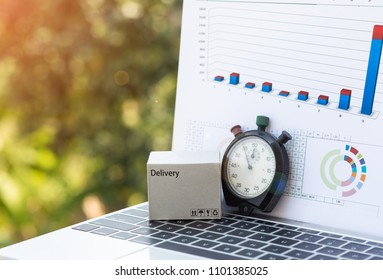 Cardboard box and stopwatch on laptop keyboard with chart and nature background. Consumers can buy products directly from seller anytime anywhere over internet. Online shopping and e-commerce concept.