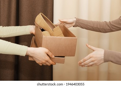 A cardboard box with suede loafers, which the hands of one girl pass to another against a draped textile yellow and brown background indoor. The concept of thrift stores, resale, second-hand.