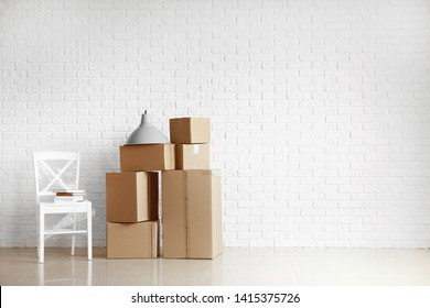 Cardboard boxes with belongings prepared for moving into new house near white brick wall