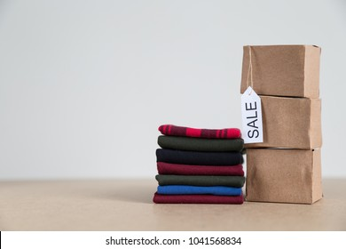 cardboard boxes and a lot of clothes on the white background for sale concept.