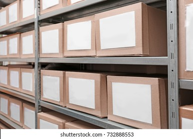 Cardboard boxes with documents on shelving unit in archive