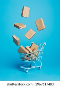 Cardboard boxes flying out of shopping trolley on vibrant blue background. Creative shop delivery service concept. Banner for online shopping or retail with copy space.