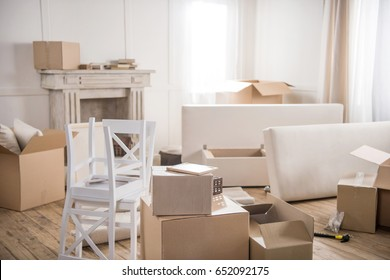 Cardboard boxes, furniture and hammer with nails in empty room, relocation concept